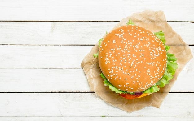Hamburger con carne di manzo, formaggio e verdure su carta su un fondo di legno bianco