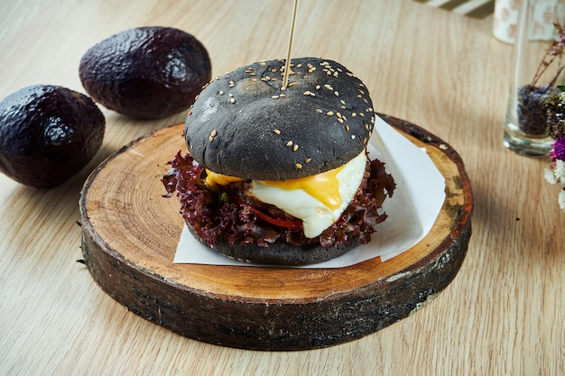 Hamburger con panini neri con uovo e formaggio fuso su una tavola di legno. visualizza. gustoso cibo da strada