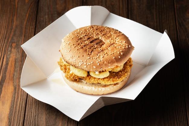 Hamburger con pollo e snack di mais croccanti si chiudono nella scatola di consegna della carta