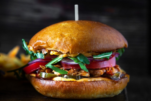 Hamburger con pollo teriyaki, pomodori e rucola su una tavola di legno