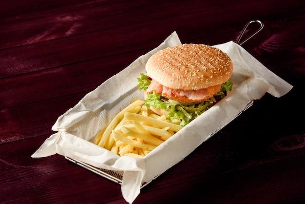Hamburger con cotoletta, pancetta, insalata, cetriolo sottaceto e patatine fritte su pergamena in un cestello di metallo su un tavolo di legno.