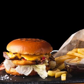 Hamburger con carne di anatra servita con patatine fritte e salsa rossa copia spazio