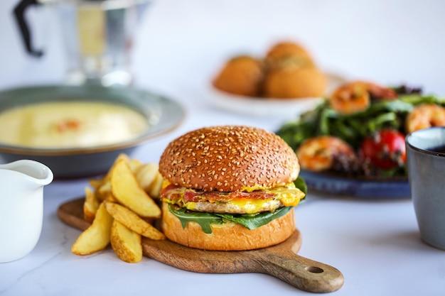 Hamburger con patatine fritte tra il cibo. hamburger con carne di manzo, formaggio, pancetta. il pranzo è sul tavolo primo piano di un hamburger con insalata, formaggio su una tavola hamburger classico giorno del pasto il cibo sul tavolo deliziosa spazzatura