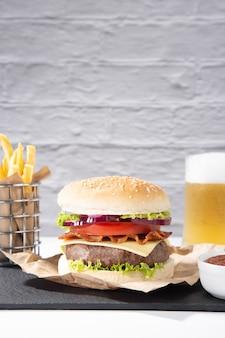 Hamburger con patatine fritte e birra su base di legno su bianco, formato verticale.