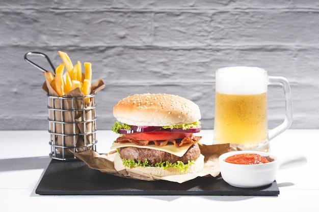 Hamburger con patatine fritte e birra su base di legno su bianco.