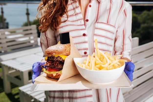 Hamburger con patatine fritte. donna dai capelli scuri che indossa elegante bella camicetta bianca che tiene hamburger con patatine fritte