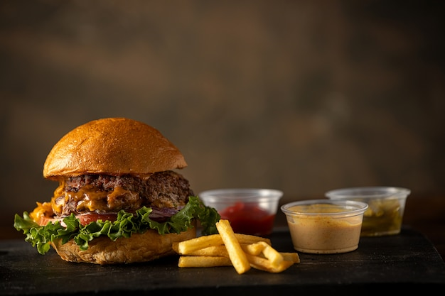 Hamburger con patatine fritte e condimento di cibo spazzatura
