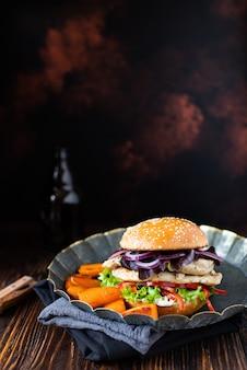 Hamburger con filetto di pollo alla griglia, paprika, patate dolci, lattuga, cipolle e yogurt greco