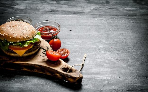 Hamburger con gli ingredienti e la salsa sulla tavola. su una lavagna nera.