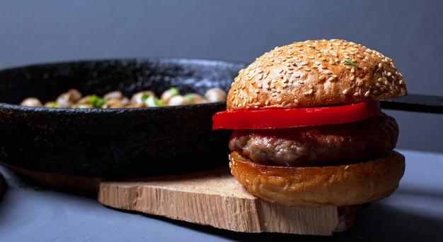 Hamburger con un panino tenero succosa cotoletta e funghi champignon in una padella di ghisa su un piatto di legno rustico su uno sfondo grigio. primo piano pranzo abbondante.