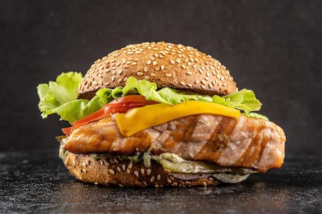 Hamburger con un grosso pezzo di salmone rosso fritto