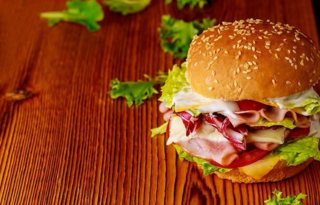 Hamburger con lattuga, formaggio, prosciutto e pomodoro su sfondo scuro. avvicinamento.