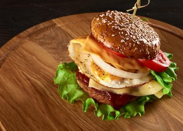 Hamburger con cotoletta di carne, formaggio, uovo fritto, pomodori, fette di cetriolo e lattuga verde, fast food su tavola di legno rotonda