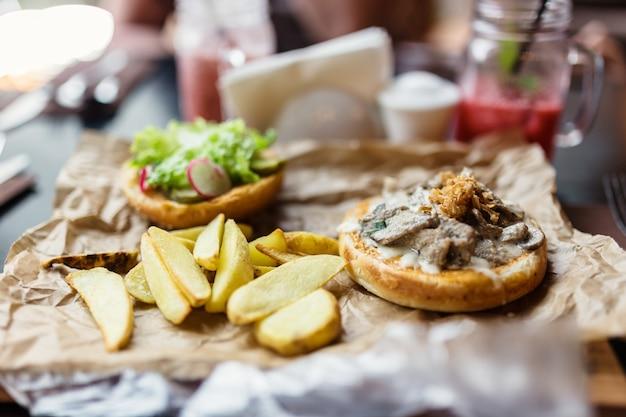 Hamburger con pezzi di manzo, cipolle fritte, patate e verdure.