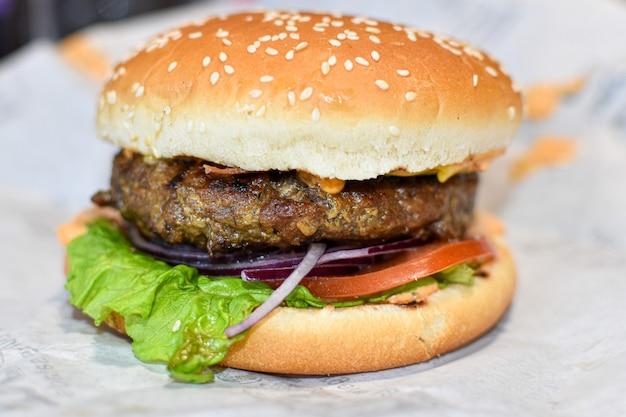 Hamburger su sfondo di carta da imballaggio. cotoletta, formaggio, verdure e panino al sesamo. fast food di strada