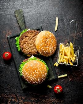 Hamburger su un tagliere nero e patatine fritte. su fondo rustico