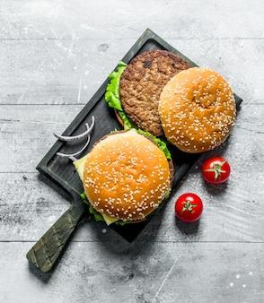 Hamburger sul tagliere nero con fette di cipolla e pomodori sulla tavola rustica bianca