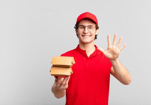 Gli hamburger consegnano il ragazzo sorridente e dall'aspetto amichevole, mostrando il numero cinque o il quinto con la mano in avanti, conto alla rovescia