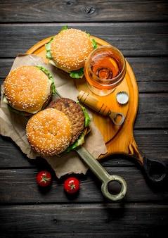 Hamburger su carta con birra e pomodori. su fondo di legno nero