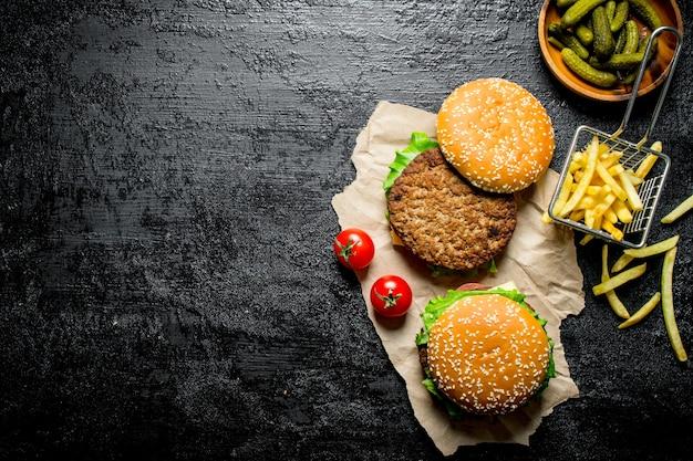 Hamburger su carta con patatine fritte, sottaceti e pomodori sul tavolo rustico