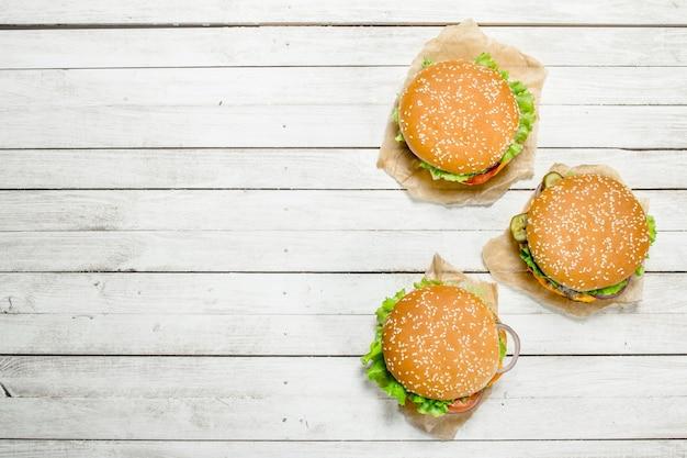 Hamburger con carne di manzo, formaggio e verdure su carta. su uno sfondo di legno bianco.