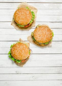 Hamburger con carne di manzo, formaggio e verdure su carta. su una superficie di legno bianca.