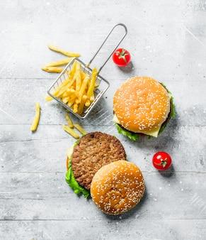 Hamburger con carne di manzo e patatine fritte sulla tavola rustica bianca
