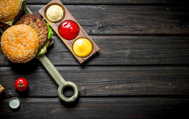 Hamburger con carne di manzo e salse. su fondo di legno nero
