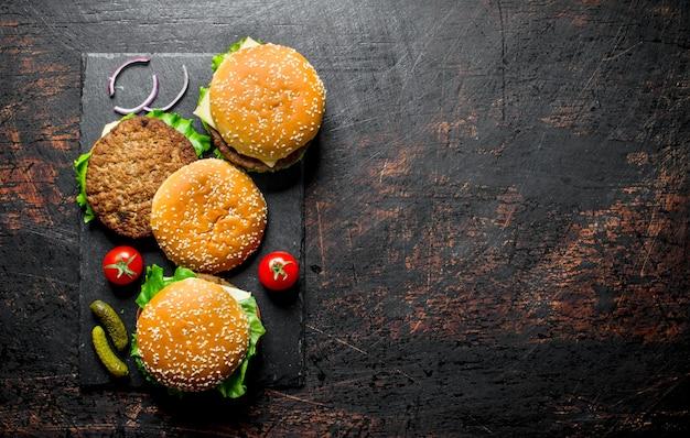 Hamburger con carne di manzo, pomodori e cetrioli. su sfondo nero rustico