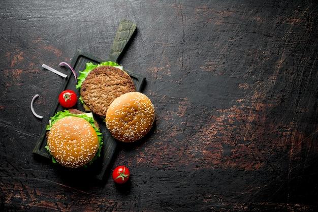 Hamburger con carne di manzo e verdure. su sfondo nero rustico