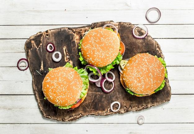 Hamburger con carne di manzo e verdure su un tagliere su un fondo di legno bianco
