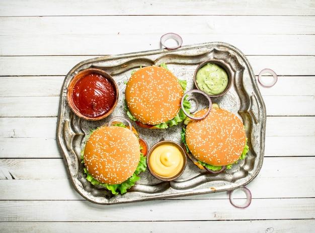 Hamburger con carne di manzo e verdure su un vassoio in acciaio su un fondo di legno bianco