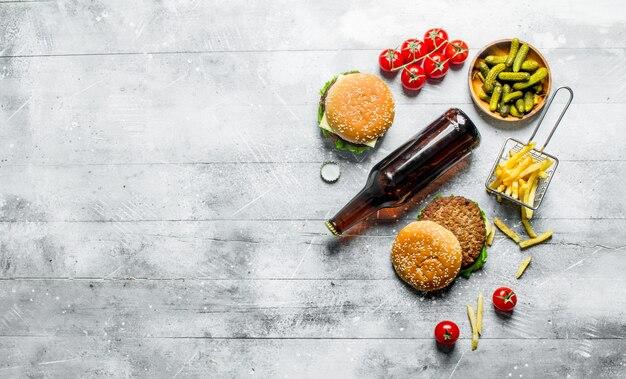 Hamburger con birra in bottiglia, cetriolini e patatine fritte sul tavolo rustico