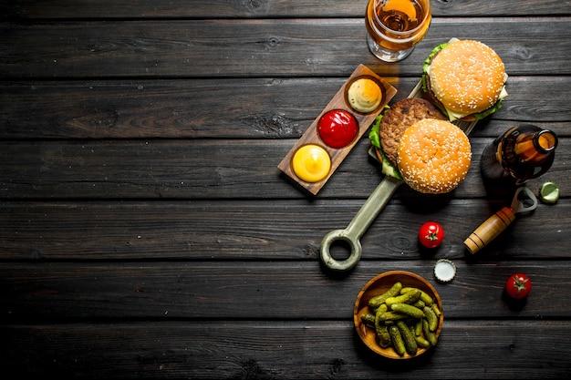 Hamburger con birra, cetriolini e salse. su fondo di legno nero
