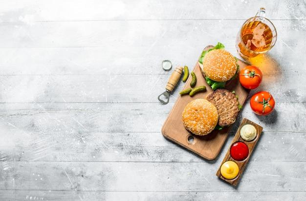 Hamburger con birra, pomodori e salse diverse. su fondo di legno bianco