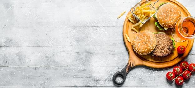 Hamburger con birra, pomodori e patatine fritte sul tagliere.