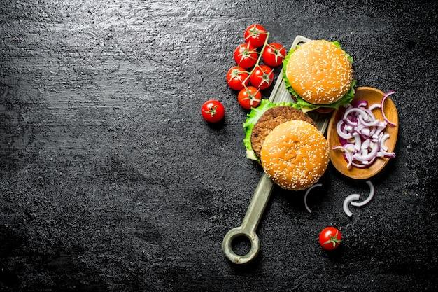 Hamburger con cipolle tritate in ciotola e ciliegia. su sfondo nero rustico