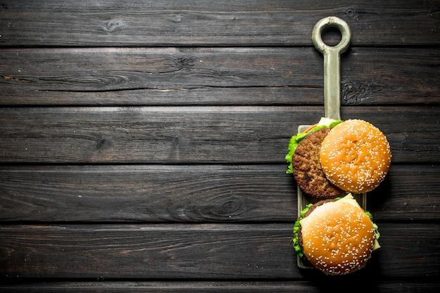 Hamburger con una cotoletta di manzo succosa, verdure e formaggio. sullo sfondo di legno