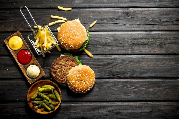 Hamburger con cetriolini in ciotola, patatine fritte e salse. su fondo di legno nero