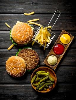 Hamburger con cetriolini in ciotola, patatine fritte e salse.