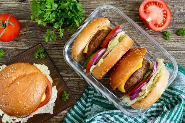 Hamburger con cotoletta succosa, verdure fresche, panino croccante con semi di sesamo su un tavolo di legno. fast food tradizionale. la vista dall'alto, piatta
