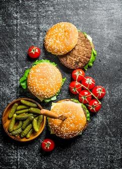 Hamburger con coltello, cetrioli e ciliegia. su fondo rustico
