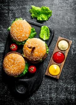 Hamburger con foglie di insalata, pomodori e salse. su sfondo nero rustico