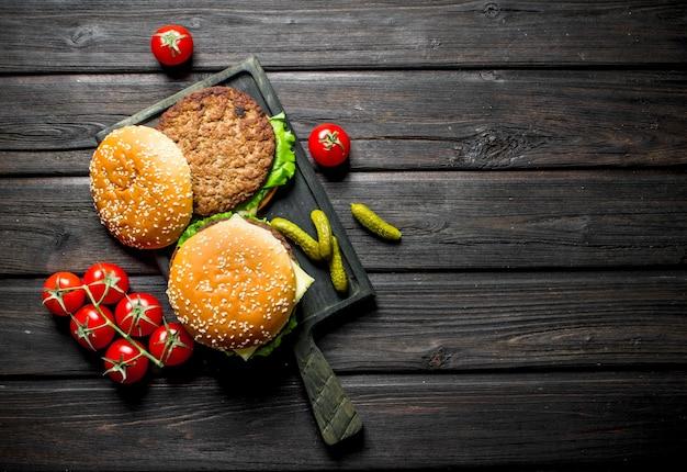 Hamburger con pomodori su un ramo e cetriolini. su fondo di legno nero