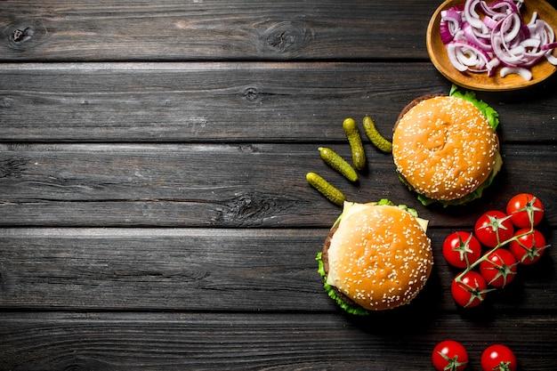 Hamburger con pomodori, cetrioli e fette di cipolla nella ciotola. su fondo di legno nero