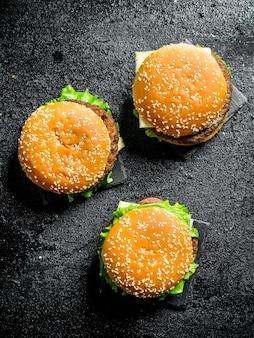 Hamburger con verdure e manzo. su sfondo nero rustico