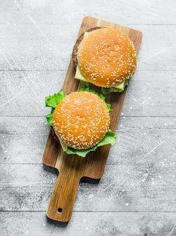 Hamburger su un supporto in legno. su fondo di legno bianco