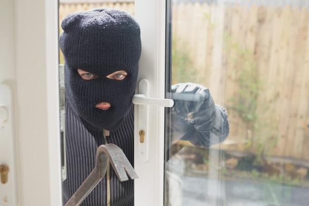 Ladro che guarda se qualcuno è nella stanza