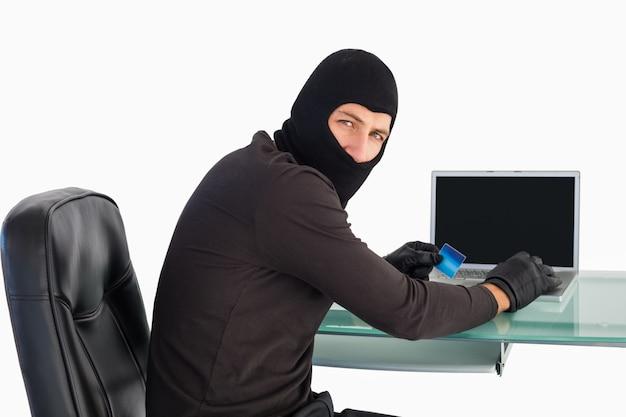 Lo scassinatore che compera online con il computer portatile mentre esamina la macchina fotografica