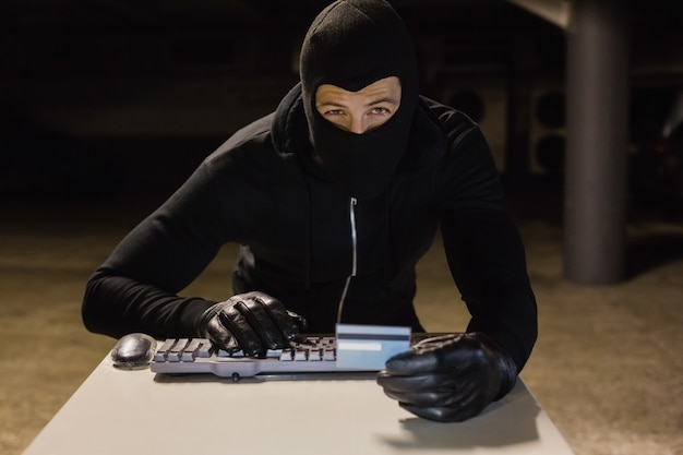 Burglar che compera online con il computer portatile